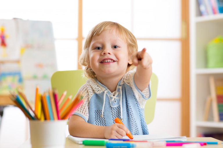 a kid playing with crayons