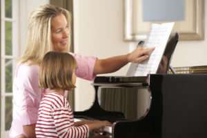 child taking piano lesson